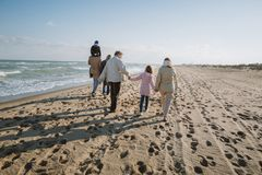 back view of parents piggybacking son while grandparents holding hands with granddaughter walking together stock photos