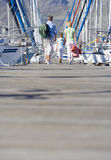 Family walking side by side in mid-distance along harbour jetty, rear view Stock Images