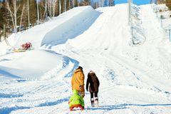 Family walking on snow hill. Rear view of couple walking towards snow slope and pulling sled with their little son on sunny winter afternoon Stock Photos