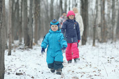 Family walking in  snowy park Stock Images