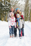 Family Walking Through Snowy Woodland. Smiling Stock Images