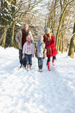Family Walking Through Snowy Woodland Royalty Free Stock Photo