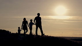 Family walking at sunset, holding hands.