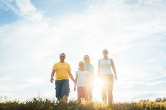 Family walking in sunset over a summer meadow royalty free stock photo
