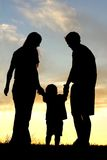 Family Walking at Sunset Silhouette. A happy family of three people, mother, father, and toddler, are holding hads and walking toward the sunset, silhouetted Royalty Free Stock Photos