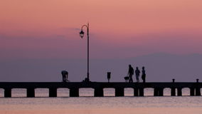 Family walking their dog on a pier at sunset Royalty Free Stock Photography