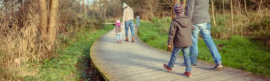 Family walking together holding hands in the forest. Back view of family walking together holding hands over a wooden pathway into the forest stock photography