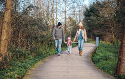 Family walking together and holding hands in the forest. Family holding hands while walking over a wooden pathway into the forest Stock Photo