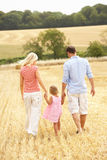 Family Walking Together Through Summer Harvested F. Ield With Back To Camera Royalty Free Stock Photography