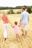 Family Walking Together Through Summer Harvested F. Ield With Back to Camera Royalty Free Stock Photo