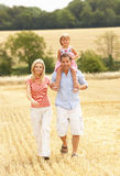 Family Walking Together Through Summer Harvested F. Ield Smiling At Camera Stock Photo