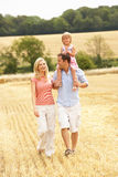 Family Walking Together Through Summer Harvested F. Ield Smiling Royalty Free Stock Photos
