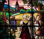 Family walking towards Church - Stained Glass Stock Image