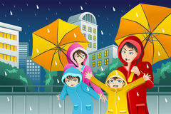 Family walking with umbrella and wearing raincoats Stock Images