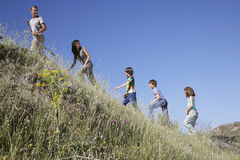 Family Walking Up Grass Slope Royalty Free Stock Photography