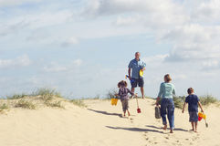 Family Walking Up Sand Dune On Beach Stock Photos