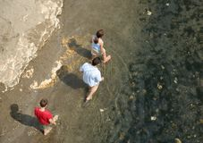 Family walking in water. Father and children walking in river edge water Stock Image