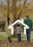 Family walking in the woods against house outline in background. Digital composition of family walking in the woods against house outline in background Royalty Free Stock Photo