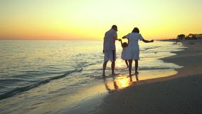 Family walks on the beach. Parents walk with their little daughter along the seashore. They hold hands. They are happy