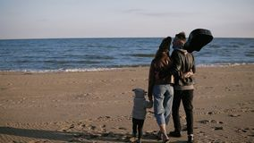 Family walks on the beach. Parents walk with their little daughter or sun along the seashore. They hold hands. They are. Happy. Father holding a guitar in hand stock footage