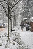 Family walks in the city  sidewalk during a copious snowfall Stock Photos