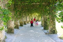A Family Walking down a Whimsical Stone Trellis Path royalty free stock image