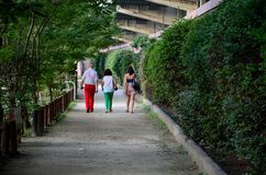 Family walks down tree and hedge lined footpath. Tokyo, Japan - September 18, 2013: A family unit, consisting of father, mother and daughter, walk down a path in Royalty Free Stock Image