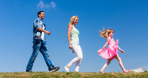 Family walks on meadow, Daughter leads, parents follow Stock Images