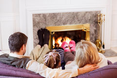 Family with warm socks. Mom, Dad and daughter warm their socked feet by the fire royalty free stock photography