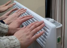 Family warming up near home electric heater stock photos