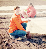 Family warms the soil with polyethylene. Happy family warms the soil with polyethylene in spring Royalty Free Stock Photo