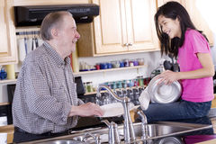 Family washing dishes. Old man and girl washing dishes Stock Images
