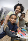 Family Washing Dishes At Kitchen Sink Stock Image