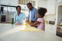 Family washing utensils in kitchen sink. At home Stock Image