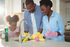 Family washing utensils in kitchen sink. At home Stock Photo