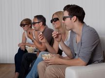 Family watching 3D television. Family with teenage children sitting together on a couch eating bowls of popcorn wearing 3d glasses and watching the television Royalty Free Stock Image