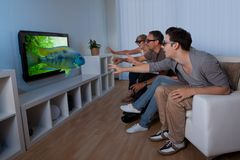 Family watching 3D television. Conceptual image of a family watching 3D television and stretching out their hands as though to touch the image on the screen Stock Photos