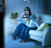 Family watching 3D TV. Mother with Daughter watching 3d film on TV Royalty Free Stock Photography