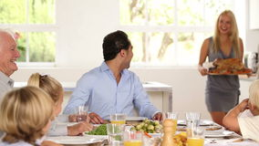 Family watching as mother brings turkey to table Stock Photography