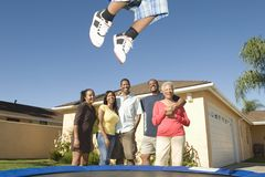 Family Watching Boy Jump On Trampoline. Happy African American family watching boy jump on trampoline stock image