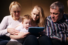 Family watching boy playing game on touchpad Stock Photo