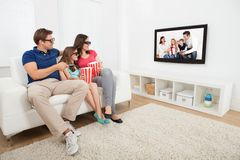Family watching 3d movie on television. Full length of family watching 3D movie on television while having popcorn at home Royalty Free Stock Photos
