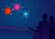 Family watching fireworks. Beautiful bright fireworks lighting up the sky as a family watches over the hills Royalty Free Stock Image