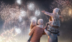 Family watching fireworks. New Year holiday. Happy family, parents and daughters children girls are watching fireworks. The child sits on the shoulders of his stock image