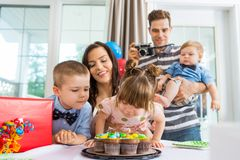 Family Watching Girl Blowing Out Candles On royalty free stock photos