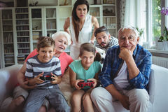 Family watching the kids playing video game Stock Images
