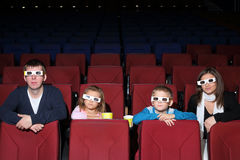 Family watching a movie in 3D cinema. With popcorn stock image