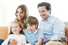 Family watching movie. Happy family watches movie while sitting on the couch Stock Photo