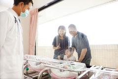 Family watching newborn in childbearing center and doctor Royalty Free Stock Photo
