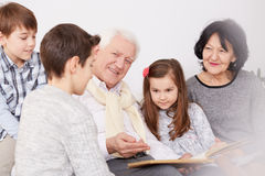 Family watching photo album. Happy family watching an old photo album royalty free stock photos